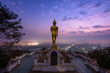 Standing Golden buddha with beautiful sunrise sky at Wat Phra That Kao Noi built during the 23rd-25th Buddhist centuries. Nan, THAILAND.