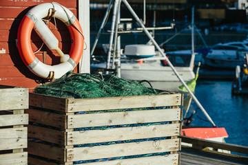 Marine lifebuoy on fence, sea background.