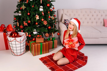 woman in hat of Santa Claus sitting with a gift