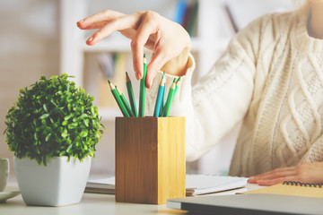 Girl taking green pencil