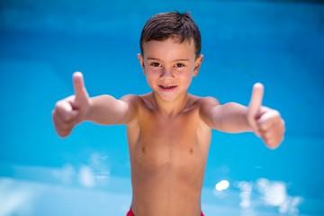 Shirtless boy gesturing at swimming pool