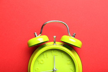 Green alarm clock on a red background