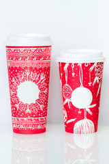 Two different paper coffee cup with red christmas pattern and em
