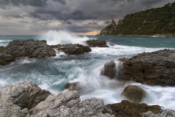 Waves crashing against rocky coast at sunset, Capo Vaticano, Italy