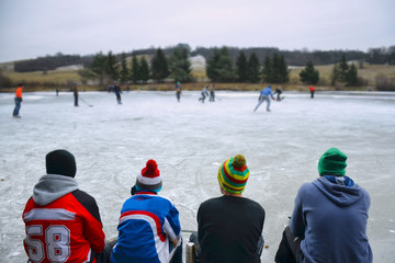 Young boys sitting on bench and looking at hockey game on natural ice. Scenery from rural sport event