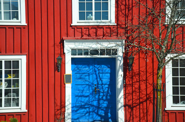 Red wall of scandinavian house with white window and tree near by house