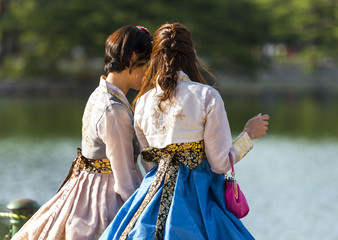 Two Korean girl dressed in old traditional dress talking at the lake in a park