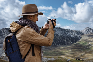 Photographer in hat  taking a picture in autumn mountains Durmit