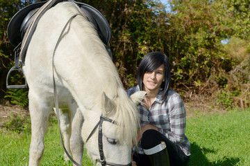 pretty young woman with white horse riding