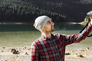 Handsome traveler taking photo at the black lake, Montenegro