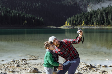 Handsome traveler with son taking photo at the black lake, Monte