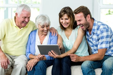 Family laughing while looking in digital tablet