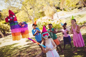 Little girl is going to broke the pinata for their birthday