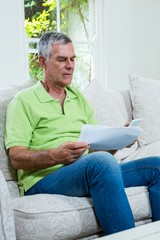 Worried senior man holding documents at home