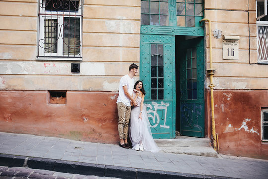 beautiful and young boy and girl stands near building