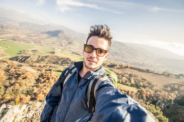 Handsome hiker taking a selfie on the top of a mountain. Concept about hiking, people, technology and lifestyle