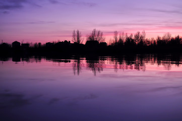 Beautiful colorful dusk on a river with silhouettes of houses and trees