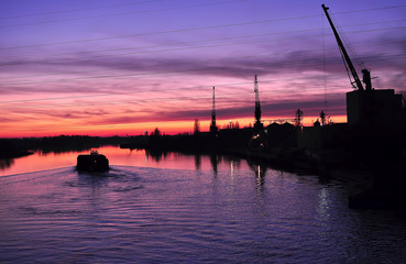 Beautiful colorful dusk on a river with silhouettes of barge and cranes