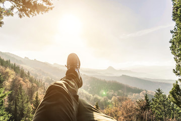 Man is enjoying the scenery on the mountain top. Pov view.
