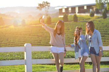Lifestyle sunny image of best friend girls taking selfie on came