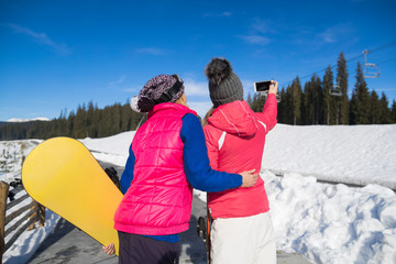 Two Woman Ski And Snowboard Resort Winter Snow Mountain Girls Taking Selfie Photo Smart Phone Holiday Extreme Sport Vacation