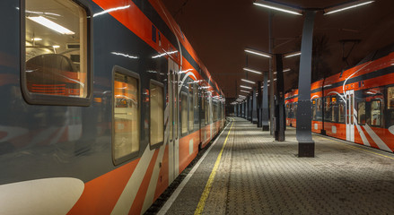 Railroad travel and transportation industry business concept: summer night view of two high speed modern passenger trains departing from railway station platform no motion, standing still