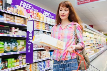 Portrait of woman putting product in shopping basket