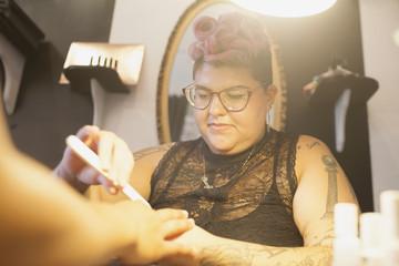 Beautician giving manicure service to customer in salon