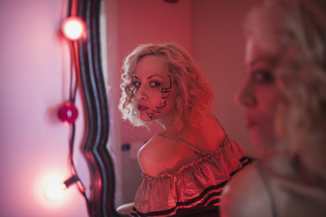 A young woman in a mirror with writing on her face.
