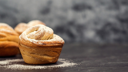 Homemade pastries cruffins, muffin with sugar powder, on dark background, selective focuse close up, copy space