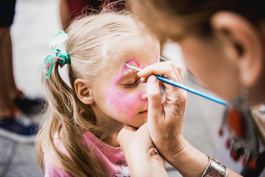 woman painting face of kid outdoors