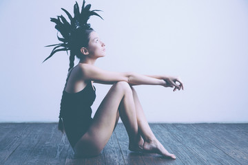 Young sexy mixed race caucasian woman vogue portrait with feather mohawk accessory wearing black bodysuit.