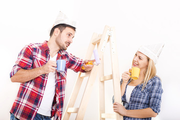 Young smilling couple painting wall in their new house. Home, moving, painting and renovating concept