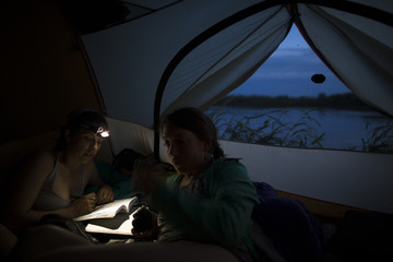Two woman spend some down time in the tent whilst camping on the river banks of the Amur river in far East Russia.