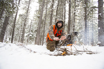 A male hunter starts a fire in the snow.