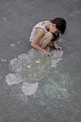 mixed race girl is drawing flower on asphalt