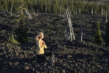 Woman practicing yoga on the lava plain