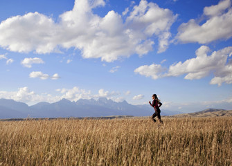 A young woman runs along a dirt road witht the Tetons in the background