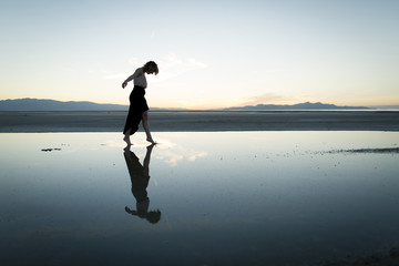 A young woman moves around the barren desert landscape of the Great Salt Lake, Utah.