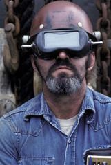 Portrait of a welder wearing a protective helmet.