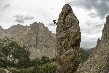 A man rappelling off of rock spire in the Sangre De Cristo Mountains, Rio Grande National Forest, Crestone, Colorado.