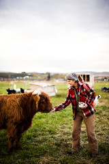 A woman feeds a furry large animal at sunrise on her farm in central Washington.