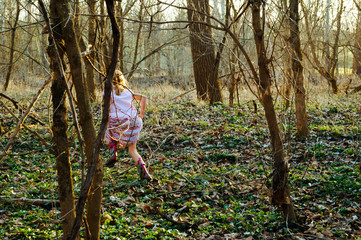 A girl runs through the woods holding her dress in Oxford OH
