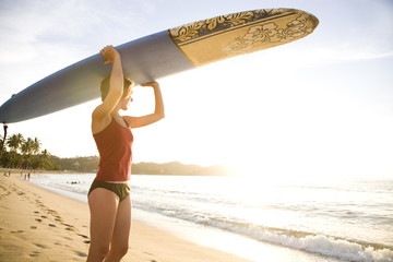 A girl wearing a red top and bikini bottoms holds a surfboard over her head on a remote beach in Sayulita, Mexico.
