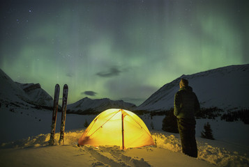 Person standing by tent looking at aurora borealis