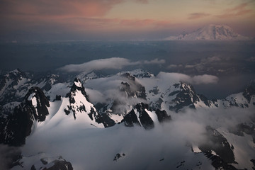 Aerial image of the Cascade Mountains covered in snow in WA at sunset.
