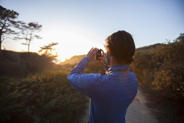 Rear view of man taking photograph of sunset with a smartphone