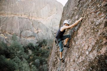 Man climbing on rocky wall, California, USA