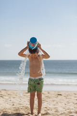 Boy throwing sea water on his head with a bucket.