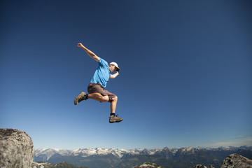 A hiker takes a running jump to cross a gap between two large granite boulders on a rocky mountain ridge.